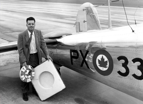 Man holding piece of equipment in front of plane