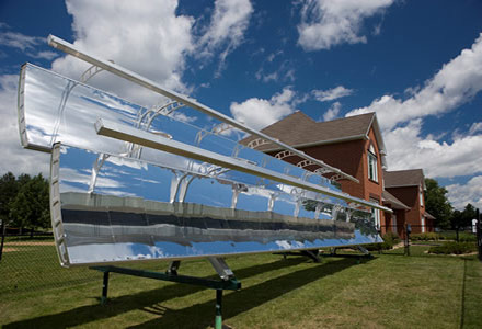 Two 5-metre long x 0.5 metre high reflective solar panels, one above the other, are on a platform next to the CCHT twin houses