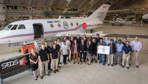 The group that worked on project standing in front of National Research Council's Falcon 20 airplane. The group includes students, National Research Council researchers, and members of Students for the Exploration and Development of Space Canada.